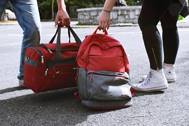 červený batoh a cestovní taška